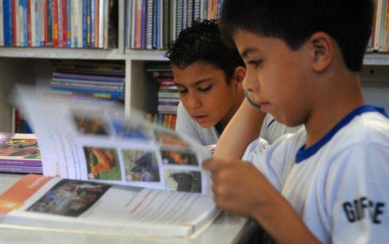 alunos lendo livro didático